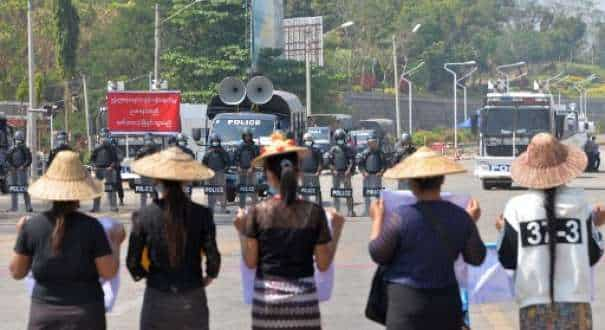 Riot police block a road in front of protesters during a demonstration against the military coup in Naypyidaw?