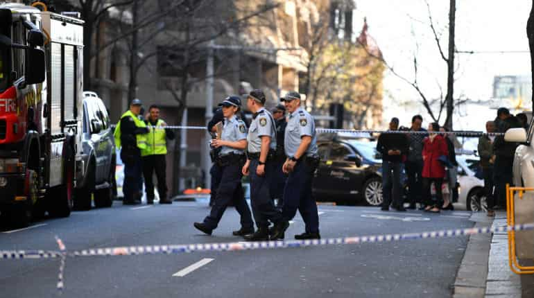 Police officers investigate a scene following reports of a stabbing in Sydney.
