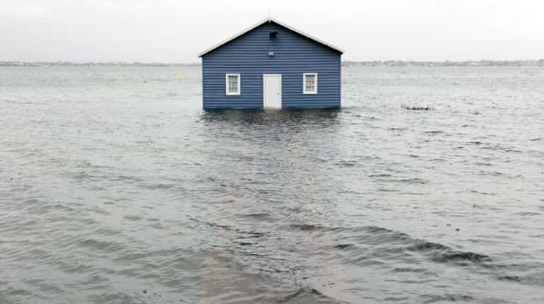 A boathouse on the Swan River sits in water in the Perth suburb of Crawley on May 25, 2020, after the area was lashed by gale force winds and a tidal surge from the remnants of Tropical Cyclone Mangga