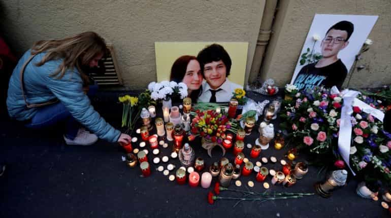 A woman kneels by a memorial of the investigative reporter Jan Kuciak and his fiancee Martina Kusnirova