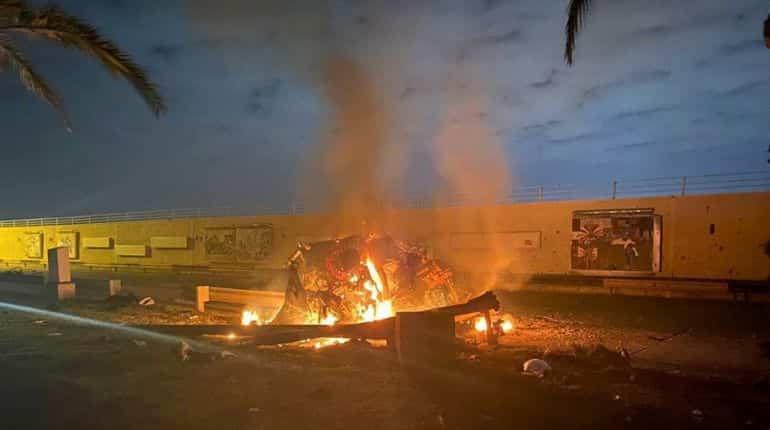Burning debris are seen on a road near Baghdad International Airport