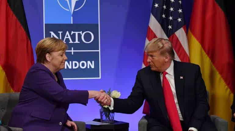 US President Donald Trump (R) shakes hands with German Chancellor Angela Merkel during a bilateral meeting on the sidelines of the NATO summit at the Grove hotel in Watford, northeast of London on December 4, 2019.