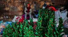 A street vendor waits for customers as he sells plastic Christmas trees at the roadside in front of the Sacred Heart Cathedral on Christmas Day, Decem