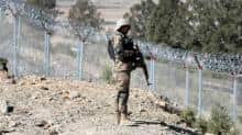 A soldier stands guard along the border fence at the Angoor Adda outpost on the border with Afghanistan in South Waziristan, Pakistan.