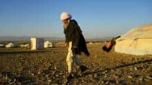 A drought-displaced Afghan man walks outside his tent at a camp for internally displaced people in Injil district of Herat province.