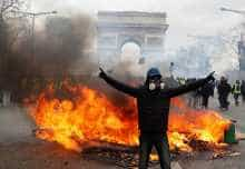 "A protester stands in front of burning barricade during a demonstration by the ""yellow vests"" movement in Paris, France, March 16, 2019."