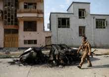 An Afghan security force walks past a burnt vehicle after Sunday's attack at the site in Kabul, Afghanistan