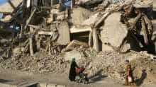 A woman pushes a baby cart as she walks past rubble of damaged buildings in Raqqa, Syria
