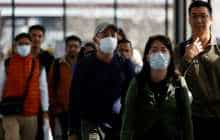 Passengers wearing masks arrive at the Tribhuvan International Airport after Nepal confirmed the first case of coronavirus