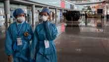 Security workers wearing protective gear as a preventive measure against the COVID-19 coronavirus walk through a nearly empty arrivals area at Beijing Capital Airport in Beijing