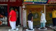 People stand on designated areas to maintain social distancing as they queue outside a medical store in Allahabad