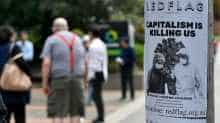 An anti-capitalist flyer is seen on a pole as people wait in a queue to receive benefit payouts, including unemployment and small business support as the novel coronavirus inflicts a toll on the economy