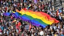 People march with their giant rainbow flag from the parliament building in Budapest downtown during the lesbian, gay, bisexual and transgender (LGBT) Pride Parade in the Hungarian capital on July 6, 2019.