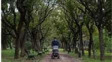 A man wearing a face mask pushes a baby carriage in a park in Seville on April 26, 2020 amid a national lockdown to prevent the spread of the COVID-19 disease