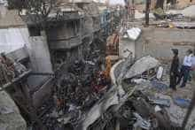 Security personnel search for victims in the wreckage of a Pakistan International Airlines aircraft after it crashed in a residential area in Karachi