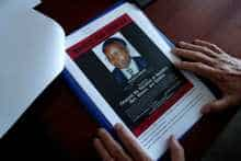 Eric Emeraux, head of the Gendarmerie's Central Office for Combating Crimes Against Humanity, Genocides and War Crimes (OCLCH), diplays documents with a wanted poster depicting a photograph of Felicien Kabuga during an interview with Reuters at his office, about the arrest of Rwandan genocide fugitive suspect Felicien Kabuga, in Paris, France, May 19, 2020