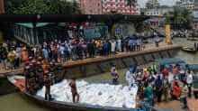 Rescue workers bring bodies of victims after a ferry capsized at the Sadarghat ferry terminal in Dhaka on June 29, 2020