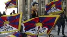 A protester wearing a costume of the Chinese President Xi Jinping stands next to others holding Tibetan flags lying on the ground as they take part in a demonstration over China's human rights record on the Trocadero esplanade in Paris on March 25, 2019, during a state visit of the Chinese president.