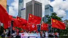 Pro-China supporters display Chinese and Hong Kong flags during a rally near the government headquarters in Hong Kong on June 30, 2020, as China passed a sweeping national security law for the city.