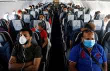 Passengers wearing protective face masks sit on a plane at Sharm el-Sheikh International Airport, following the outbreak of the coronavirus disease (COVID-19), in Sharm el-Sheikh, Egypt, June 20, 2020