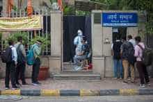 People line-up while a health official wearing a Personal Protective Equipment (PPE) suit collects a swab sample in Delhi