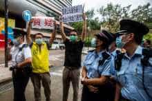 Police officers look at pro-democracy district councillors protesting against the government's decision to have mainland inspectors carry out COVID-19 testing
