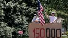 "A man holds a U.S. flag and a sign reading ""150 000"" to represent the number of victims of the coronavirus disease (COVID-19) in the U.S., while U.S. President Donal Trump plays golf at Trump National Golf Club, in Sterling, Virginia, U.S., August 2, 2020"
