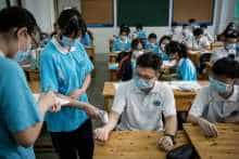 A student checks the body temperature of her classmates in a classroom in a high school in Wuhan