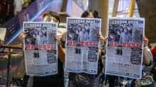 People hold up copies of the Apple Daily as they protest for press freedom inside a mall in Hong Kong on August 11, 2020, a day after authorities conducted a search of the newspaper's headquarters after the company's founder Jimmy Lai was arrested under the new national security law.
