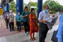 Commuters wait in a queue to enter a metro station in Delhi
