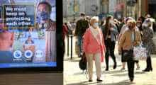 Shoppers, some wearing a face mask or covering, walk past an electronic billboard displaying a UK Government advert advising the public to take precautions to mitigate the spread of COVID-19, in Newcastle