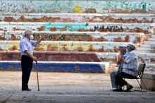 Elderly Spanish men chat in a square in the neighbourhood of Vallecas in Madrid