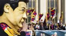 A protester wearing a costume of the Chinese President Xi Jinping gestures while others hold Tibetan flags as they take part in a demonstration over China's human rights record on the Trocadero esplanade in Paris on March 25, 2019, during a state visit of the Chinese president.