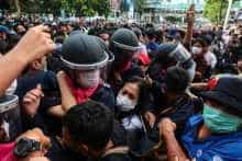 Pro-democracy protesters scuffle with the police as another gives the three-finger salute in Bangkok
