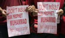 Muslim protesters hold placards during a demonstration against Swedish artist Lars Vilks, whose sketch had shown the Prophet Mohammad with the body of a dog, outside the Swedish embassy in Kuala Lumpur