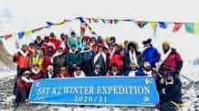 This handout photo taken on January 16, 2021 and released by Seven Summit Treks, shows mountaineers and Sherpas posing for pictures after reaching the summit of Mt K2, which is the second highest mountain in the world.