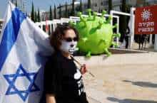 A protester carries an Israeli flag near an inflatable balloon depicting a COVID-19 coronavirus virion particle