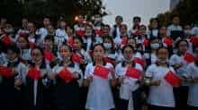 Students wearing face masks as a preventive measure against the Covid-19 coronavirus hold national flags as they rehearse a song in a park next to the Yangtze River in Wuhan, in China's central Hubei province on September 25, 2020.