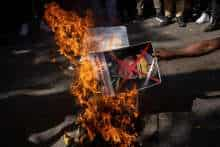FILE PHOTO: A Myanmar citizen living in India burns a poster of Myanmar's army chief Senior General Min Aung Hlaing with his face crossed out