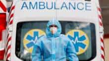 A medical worker wearing protective gear stands next to an ambulance outside a hospital for patients infected with COVID-19 in Kyiv, Ukraine, November 24, 2020