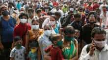 People wearing protective masks stand outside a railway station amidst the spread of the coronavirus disease (COVID-19), in Mumbai, India, April 13, 202
