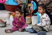 Palestinan children eat as families took shelter at a United Nations (UN) school in Rafah in the southern Gaza Strip