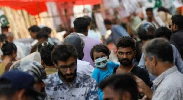 A girl, wearing a protective mask, and her father are seen in a rush of people, ahead of Pakistan's Independence Day, as the coronavirus disease (COVID-19) pandemic continues, in Karachi, Pakistan August 9, 2020