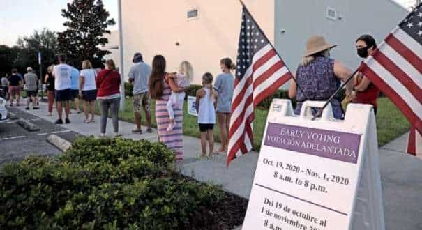 People line up to cast their ballots shortly after sunrise during early voting session in Celebration, Florida, US