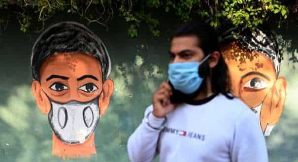 A man wearing a facemask as a preventive measure against the Covid-19 coronavirus speaks on his mobile phone while walking past a mural along a roadside in New Delhi