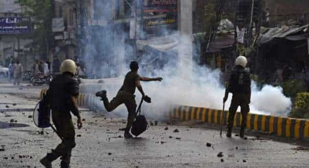 A file photo of a policeman throwing a stone towards supporters of Tehreek-e-Labbaik Pakistan (TLP) during a protest in Lahore, after the arrest of their leader, who has called for the expulsion of the French ambassador.